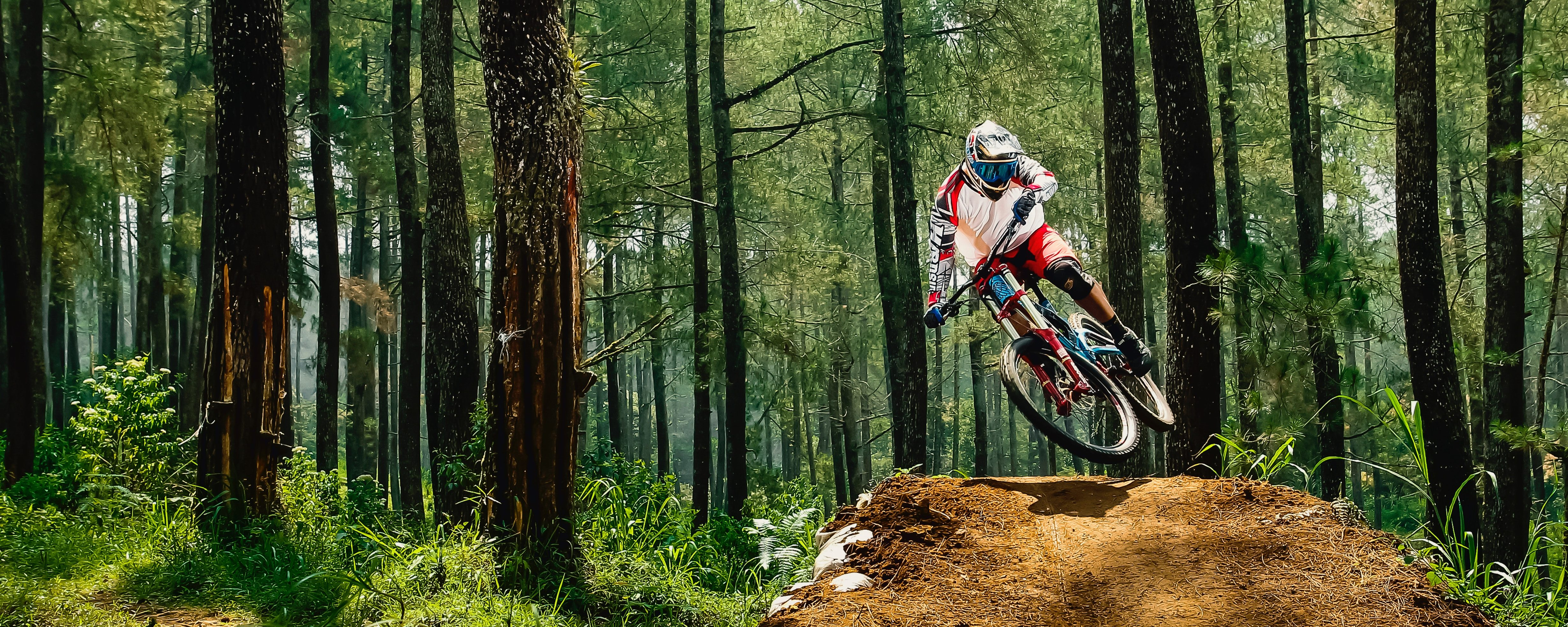 Professional mountain biker performing risky jump in forest