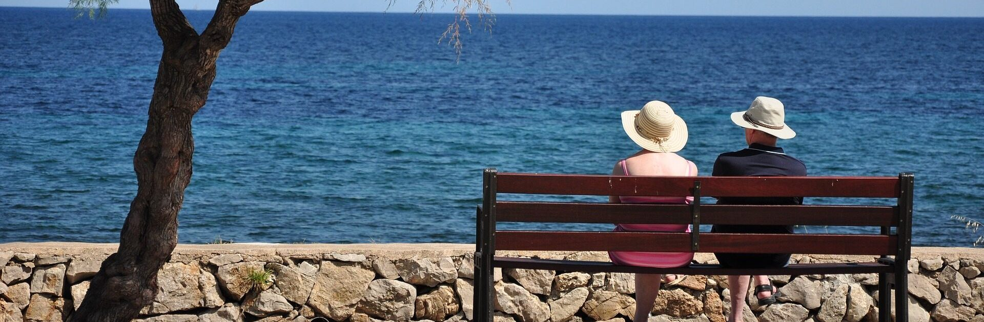 An elderly couple sat on a bench facing the sea, enjoying the view.